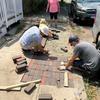 Group laying bricks on sidewalk