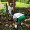 Kids moving rocks around garden bed