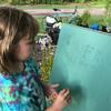 Child writing Beaver Ponds Park on an easel