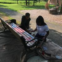 Two volunteers spray painting bench