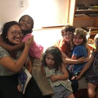 Group of children, one hugging an adult