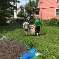 Volunteers carrying garden waste bag